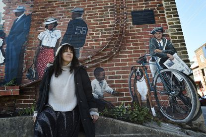 """Antonia Ramis Miguel, 56, of Ellicott City, sits in front of her """"Car Dealership: Looking into the Past"""" mural on the east wall of Sweet Elizabeth Jane at 8289 Main St."""