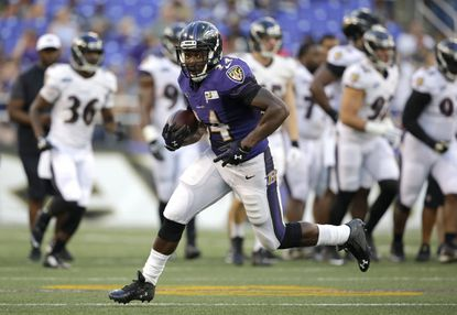 Ravens running back Lorenzo Taliaferro rushes the ball during NFL training camp last year.