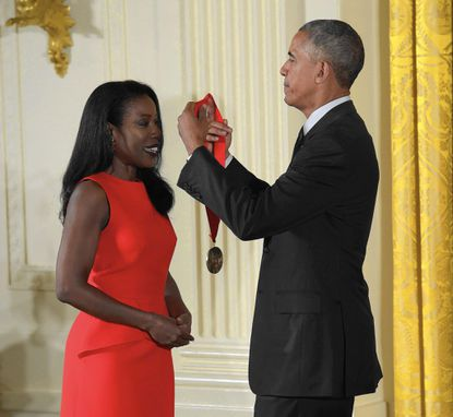 """Pulitzer Prize-winning journalist Isabel Wilkerson receives the National Humanities Medal from President Barack Obama during a ceremony in 2015. In her new book """"Caste,"""" she explores if white people put their race before their best interest in choosing candidates."""
