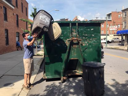 Chris Mardekian of Baltimore's Butchers Hill neighborhood puts his recycling into one of the temporary dumpsters placed by the city last year. (Barbara Haddock Taylor/Baltimore Sun).