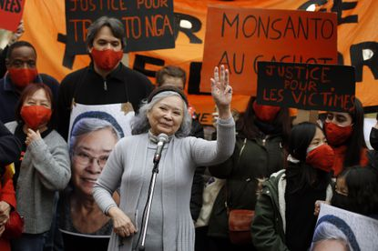 Tran To Nga, a 78-year-old former North Vietnamese journalist, waves as she delivers a speech during a gathering in support of people exposed to Agent Orange during the Vietnam War, in Paris, Jan. 30, 2021. (AP Photo/Thibault Camus)