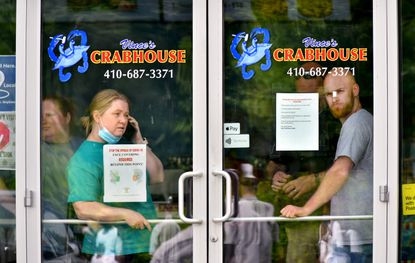 Vince Meyer, right, owner of Vince's Crab House, and his mother, left, peer through the window of the Middle River takeout restaurant at protesters on Monday. A man was arrested in the parking lot Saturday night for threatening demonstrators with a bat, Baltimore County Police said.
