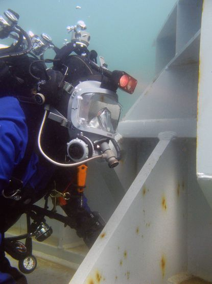 A diver in the UNDEX Test Facility at Aberdeen Proving Ground, known as the Super Pond.