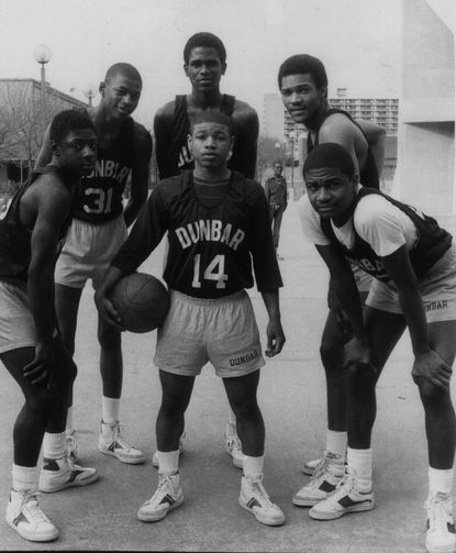 "From left: Darryl Wood, Reggie Lewis, Reggie Williams, Tim Dawson and Jerry White. At the center, with the ball, is Tyrone Curtis ""Muggsy"" Bogues. The group formed the core of the 1982-1983 Dunbar High School basketball team."