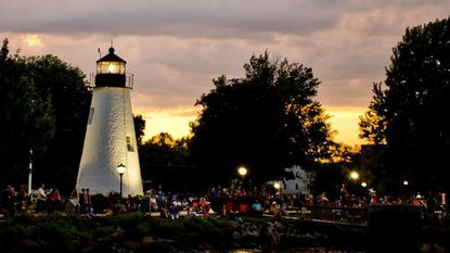 Attendees start to fill the promenade along the water by the lighthouse before the start of the annual Havre de Grace Fireworks celebration at Concord Point in Havre de Grace on July 2, 2017.