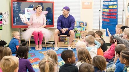 Pinkalicious, also known as Nicole Salla, Peteriffic, or Josh Frick, reads books to children at Kiddie Academy.