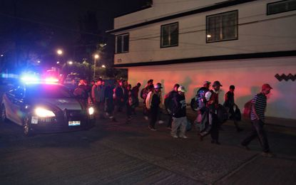 Central American migrants taking part ina caravan toward the United States are escorted by a police car Thursday in Puebla, Mexico.