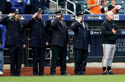 Orioles manager Buck Showalter and members of the NYPD salute as the national anthem is played before the game between the New York Mets and the Baltimore Orioles on May 5, 2015 at Citi Field in Queens, N.Y. The New York Mets held a moment of silence in honor of slain Queens officer, Brian Moore.