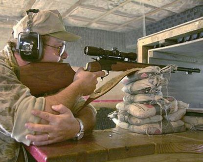 Ray Cox practices at the Carroll County shooting range to get ready for deer season. He is aiming at a target 50 yards away.
