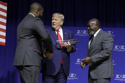 "President Donald Trump is awarded the Bipartisan Justice Award by Matthew Charles, right, one of the first prisoners released by the First Step Act, during the ""2019 Second Step Presidential Justice Forum"" at Benedict College, Friday, Oct. 25, 2019, in Columbia, S.C. (AP Photo/Evan Vucci)"