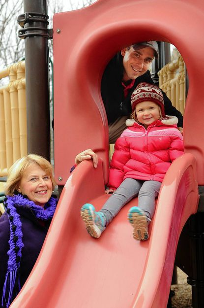 Miki Federline of Towson Manor Village, left, poses for a picture with her son Dave Federline and his 3-year-old daughter Brenna at Towson Manor Park in Towson on Dec. 20. The family fought for the park 25 years ago after Dave, at the age of ten, was hit by a car coming from the nearest open space. They are hoping to keep the park from becoming the location of a newly proposed fire station.