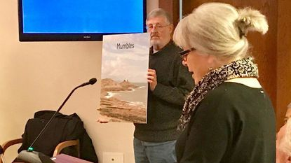 Debby Stathes, of the Havre de Grace Twinning Association, discusses the 'Twinning' relationship between Mumbles, Wales, and Havre de Grace, while her husband, Chris, holds a photo of the town's coastline and lighthouse, during the Havre de Grace City Council meeting Monday.