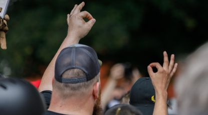 "A member of the far-right Proud Boys group makes the ""OK"" hand gesture at a rally in Portland on Aug. 17, 2019."