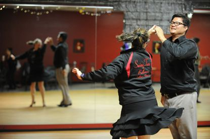 Instructor Froilan Mate, right, practices a competition routine with student Gina Kazimir during a ballroom dancing lesson at SwingTime Ballroom in Fallston.