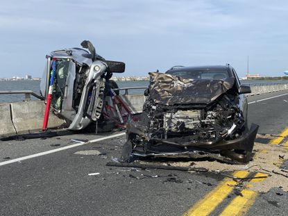 This photo provided by the Ocean City Fire Department shows the wreckage from a car accident on the Route 90 bridge in Ocean City on Sunday, May 2, 2021. A bystander jumped over a highway guard rail and into the water below to rescue a child who had been thrown from a car and into Assawoman Bay during the crash, according to authorities. (Ocean City Fire Department via AP)