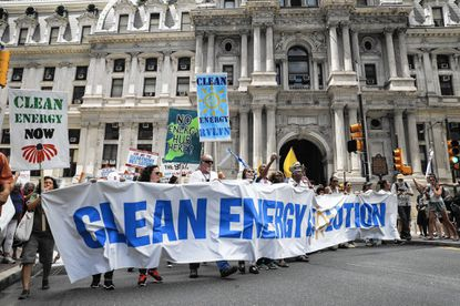 Climate change activists carry signs as they march during a protest in downtown on Sunday, July 24, 2016, in Philadelphia. The Democratic National Convention starts Monday in Philadelphia. (AP Photo/John Minchillo)