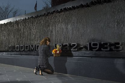 First lady of Ukraine Maryna Poroshenko presents flowers during the unveiling and dedication of the Holodomor Memorial in Washington, D.C. Buses of Baltimore-area residents attended the memorial unveiling, including Andrij W. Chornodolsky, who lives in Timonium and was involved with the committee behind the memorial.