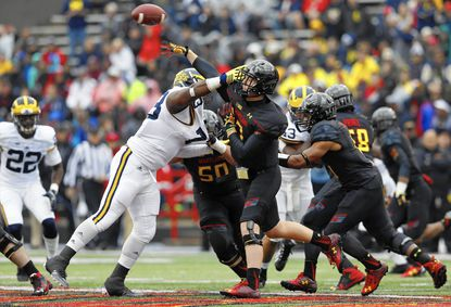Maryland quarterback Caleb Rowe, right, throws a pass as he is pressured by Michigan defensive tackle Maurice Hurst in the first half of an NCAA college football game, Saturday, Oct. 3, 2015, in College Park, Md. (AP Photo/Patrick Semansky)