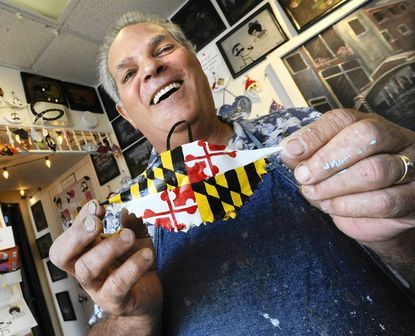 Tom Matarazzo, who paints crab shells, holds his best seller, featuring the Maryland flag.