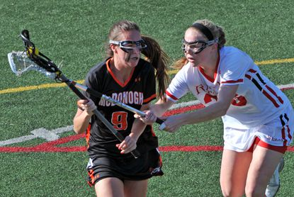 McDonogh's Savannah Buchanan, carrying ball, left, tries to evade Roland Park's Anna Hauser on March 26. Buchanan is aiming for a seventh consecutive IAAM A Conference title, having played on the past two champion soccer, basketball and lacrosse teams.