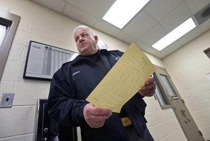 """In this 2017 photo, Frederick County Sheriff Chuck Jenkins shows an intake form that include the questions """"What Country were you born in? and What Country are you a citizen or national of?"""" his officers use at Central booking. Frederick County Sheriff co-operate with the U.S. Immigration and Customs Enforcement (ICE) in their detention center through the Fed's 287g program."""