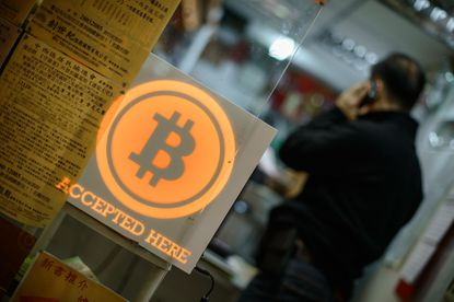 A man talks on a mobile phone in a shop displaying a bitcoin sign during the opening ceremony of the first bitcoin retail shop in Hong Kong in this February 28, 2014, file photo.