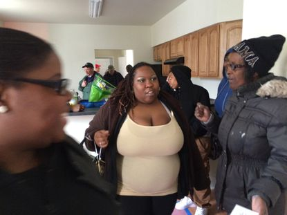 LaKeisha Hunt, center, tours her new home built by Habitat for Humanity volunteers. The site for her home was among the first demolitions under Mayor Stephanie Rawlings-Blake's Vacants to Values program in 2011.