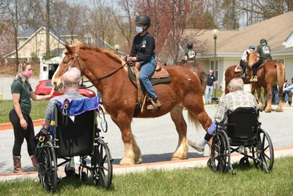 Shelby Piovoso, left, head trainer at Gentle Giants Draft Horse Rescue, leads Pecan, a Belgain mare, and rider Bonnie Douglas past residents at the Lorien Mount Airy, as they visited the retirement community on Tuesday, April 6, 2021.