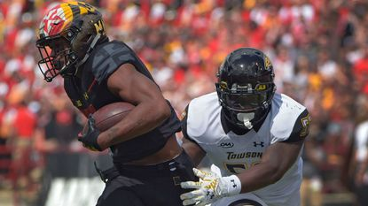 Terps wide receiver D.J. Moore breaks away from Towson linebacker Diondre Wallace to score a touchdown during Maryland's first home game of the season on Sept. 9.