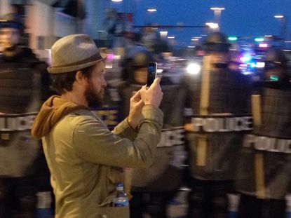 Baynard Woods captures media of police officers in riot gear during the Baltimore Uprising