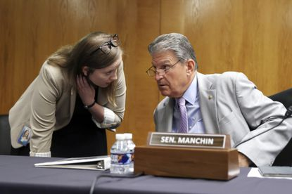 Sen. Joe Manchin, D-W.Va., left, speaks with an aide during a Senate Appropriations Subcommittee hearing, Wednesday, June 9, 2021, on Capitol Hill in Washington, D.C. (Tasos Katopodis/Pool via AP)