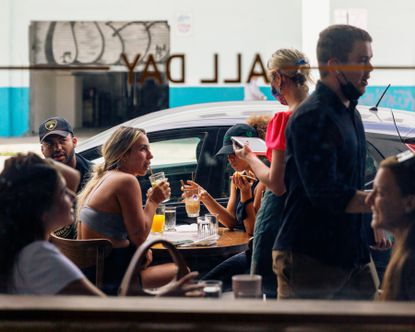 Patrons dine outside at All Day, a coffee shop and restaurant in Miami, April 6, 2021. Restaurant owners across the country are reporting a shortage in help, as rebounding business forces them to compete for a shrunken pool of applicants.