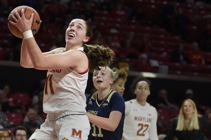 Maryland's Taylor Mikesell drives to the basket as George Washington's Tori Hyduke follows on Wednesday, Nov. 20, 2019 in College Park.