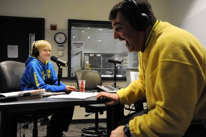 Radio host Booker Corrigan, right, laughs at an on-air comment by Cullen Little, left, 12, during a live broadcast of the Booker Corrigan Show on CBS Sports Radio 1300 WJZ-AM on Thursday, Jan. 24. Cullen co-hosts the show.