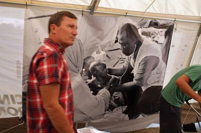"""A visitor examines the Doctors Without Borders exhibit """"Starved for Attention"""" on Sept. 13 in Union Square in Manhattan. The same exhibit came over the weekend to Baltimore's Patterson Park."""