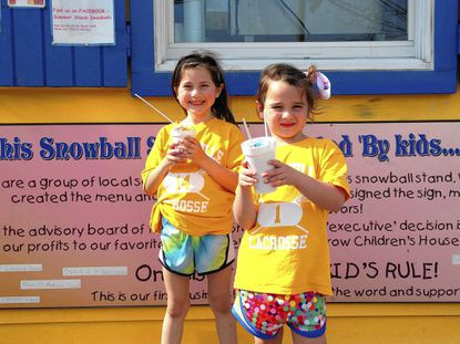 Laurel Robinson, 6, left, and Piper Morris, 5 enjoy a cool treat at Summer Shack Snoball Stand after their game with Lutherville-Timonium rec council lacrosse game on a recent Sunday.