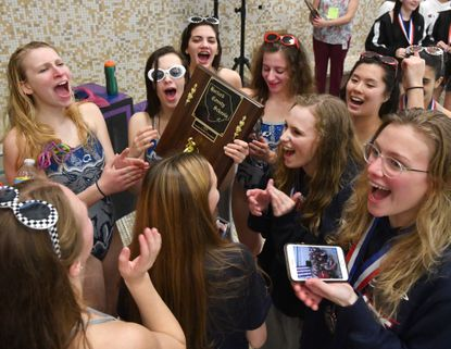 Members of the Bel Air High School girls swim team celebrate their win during Wednesday evening's girl's District VII swim championship at Magnolia Middle School.