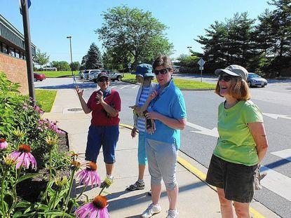 In 2013, Master Gardener Andrea Kowaleski, of Eldersburg, describes some of the features of the Eldersburg library's native plant garden to Anita Leamy, of Eldersburg; Mary Bosch, of Sykesville; and Peggy Dash, of Winfield, another Master Gardener.
