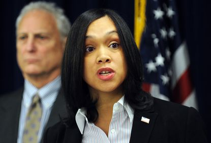 Deputy Chief Michael Schatzow stands behind Baltimore City State's Attorney Marilyn Mosby during a February news conference.