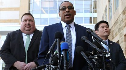 FBI Special Agent Gordon Johnson, center, speaks while flanked by U.S. Attorney Robert Hur, right, and Art Walker of the Coast Guard Investigative Service, after a hearing at the United States District Court Greenbelt Division.