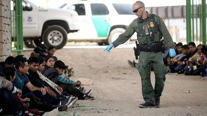 A U.S. Border Patrol agent gestures towards migrants being detained after crossing to the U.S. side of the U.S.-Mexico border barrier on May 19, 2019 in El Paso, Texas.