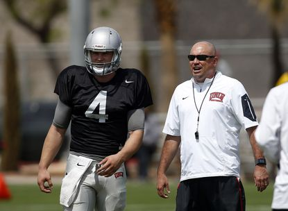 UNLV football head coach Tony Sanchez, right, talks with quarterback Johnny Stanton during the Rebels' spring game.