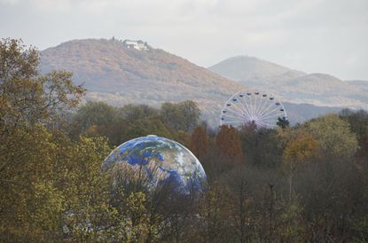 A globe and a Ferris Wheel stand in the forest near Bonn, Germany, on Nov. 13, 2017. The UN Climate Conference takes place in Bonn, Germany till Nov. 17, 2017.