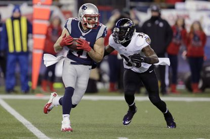 New England Patriots wide receiver Julian Edelman runs from Ravens strong safety Will Hill after catching a pass in the first half of an NFL divisional round playoff game.