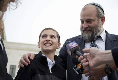 In this Nov. 3, 2014 file photo, Menachem Zivotofsky and his father Ari Zivotofsky speaks to media outside the Supreme Court in Washington. The Supreme Court has struck down a disputed law that would have allowed Americans born in Jerusalem to list their birthplace as Israel on their U.S. passports.