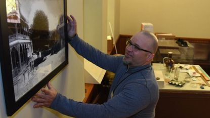 At the Museum of Howard County History, Shawn Gladden, executive director of the Howard County Historical Society, is setting up an exhibit about Ellicott City's Main Street through the ages. Here, he straightens one of many historic photos that will be on display.