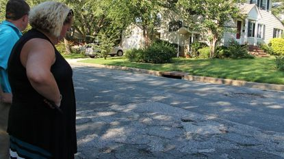 Kyra Vocci, the president of the Greenbrier Community Association examines a rough patch of road in the neighborhood last month. County officials say they will begin repaving the roads in the spring.