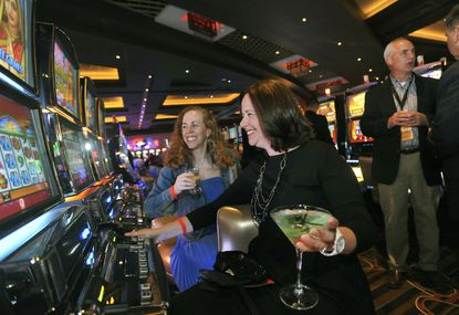 Jodi Miller (black dress) and Diana Terrill were some of the VIP guests who were allowed into the new Maryland Live Casino to start playing slot machines early. Baltimore Police Commissioner Frederick H. Bealefeld III is in the background.