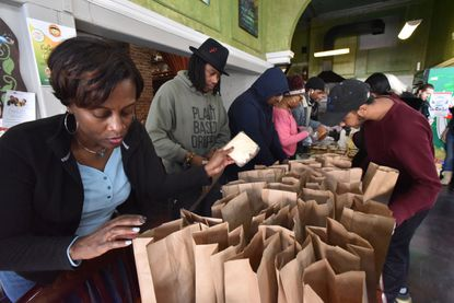 There's a lot we can do: Neighbors Without Walls volunteers meet at Terra Cafe to pack lunches to deliver to Baltimore's homeless.