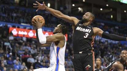 Oklahoma City Thunder forward Jerami Grant, left, goes up for a shto around Miami Heat guard Dwyane Wade (3) in the second half of an NBA basketball game, Monday, March 18, 2019, in Oklahoma City. (AP Photo/Kyle Phillips)
